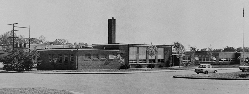 Black and white photograph of the front of Wakefield Forest Elementary School taken in 1965. The building looks relatively new and small trees have been planted all along the front. Two early 1960s era cars are parked in front of the building.